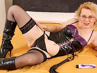 Blond granny in a domina outfit masturbates in her daybed
