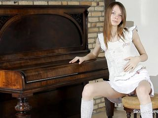 slim girl at the piano behaves naughty