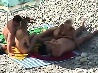 2 tanned couples have enjoyment on a beach